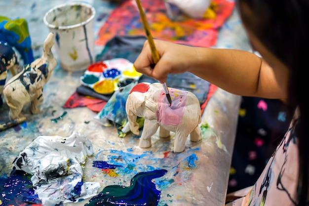ペイントブラシの研究を保持し、美術教室で木の動物の人形に塗料を学ぶ美術学生のクローズアップ手。
