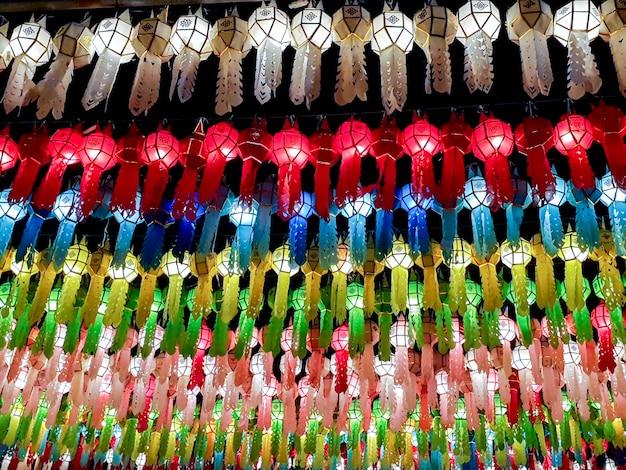 ロイクラトンフェスティバルの夜の時間に寺院の前に吊るすタイのランナスタイルのランタンのカラフルなルックアップビュー。