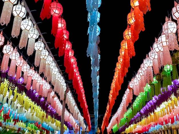 ロイクラトンフェスティバルの夜の時間に寺院の前に吊るすタイのランナスタイルのランタンのカラフルな視点とルックアップビュー。