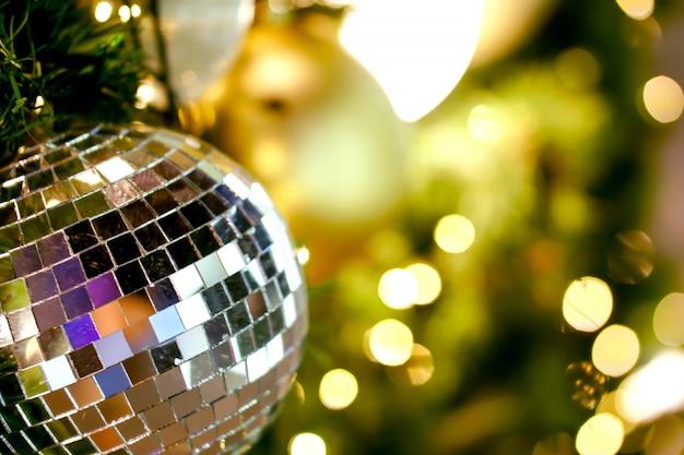 ぼやけてクリスマス照明背景のボケ味のクリスマスの日に松の木に飾られたクリスマスボールのクローズアップクリスタル。