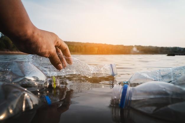 Доброволец забирает бутылку из пластика в реку, защищает окружающую среду от загрязнения.