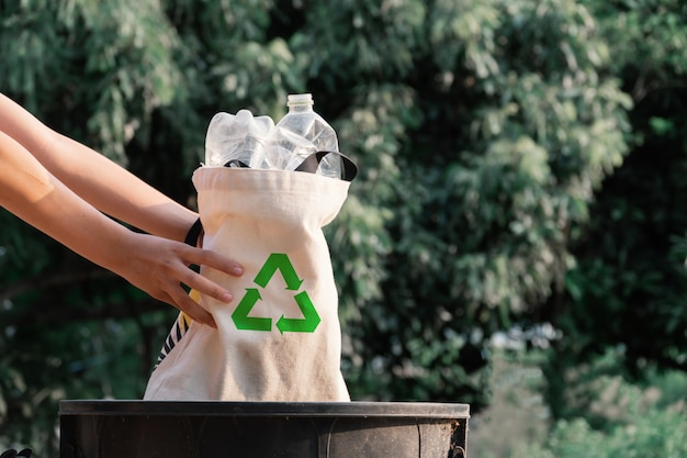 ビンにビニール袋を保持しているボランティア