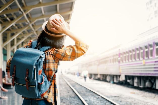 アジアの女性のバックパッキング鉄道駅、休日の概念の旅の旅を開始します。