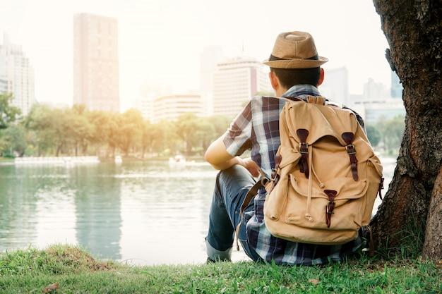 アジア人の男性が公園、休暇の概念の旅にツリーの下に座ってバックパッキング。