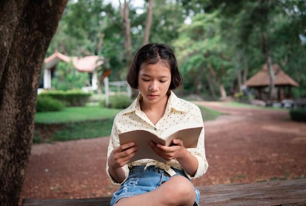 アジアの女の子が公園で本を読んで