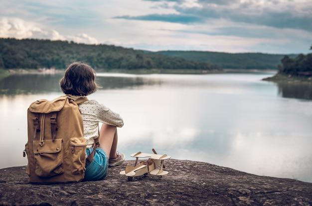 湖のそばのバックパックと飛行機モデルを持つ若い女性