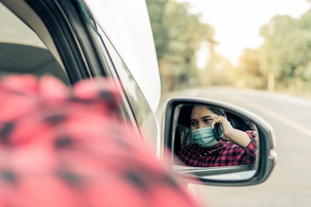 車が壊れている間、若い女性が保険をかけます。