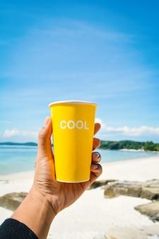 クールな単語の海と青い空の背景と黄色のカップを保持して女性の手