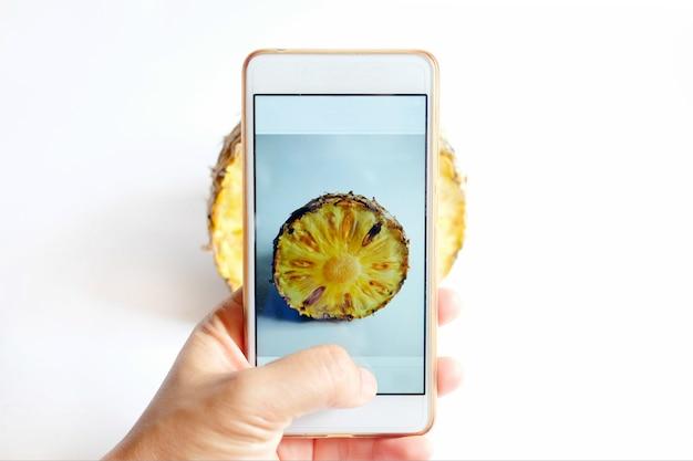 携帯スマートフォンを持ち、パイナップルの写真を撮る手