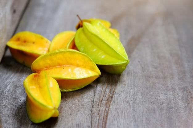 Спелая желтая звезда или фруктовое яблоко, карамбола на деревянном полу