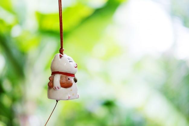 マネキ猫は緑の自然の背景を持つウィンドウに掛かっている日本のラッキーキャット人形です。