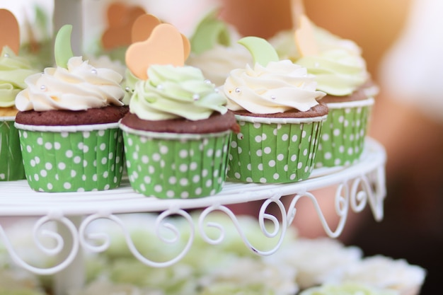 ガーランドライトボケ味と日光の背景を持つグリーンカップで結婚式のチョコレートカップケーキ