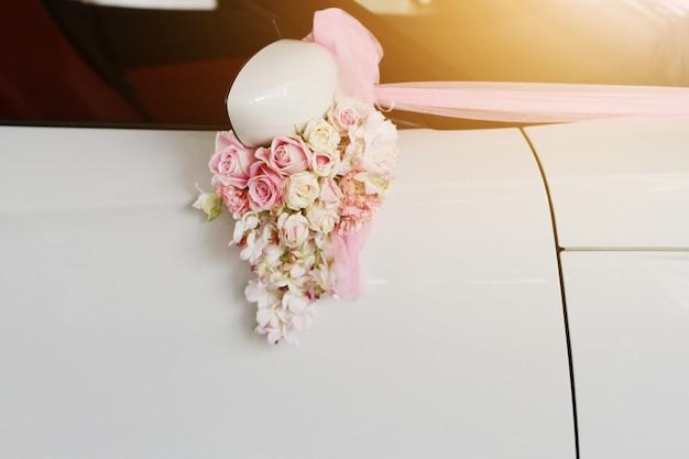 結婚式のための白い車のドアハンドルに飾られた美しいピンクのバラの花のリボン
