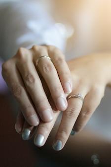 伝統的なタイ式結婚式で結婚指輪を花嫁の手を繋いでいる新郎手。
