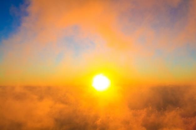 森の中の黄金の光と朝の霧の中で日の出と山。タイのジャングルの丘を覆う霧