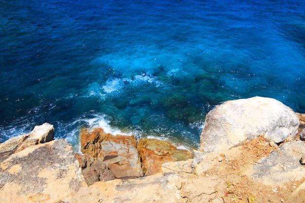 Прекрасное райское лето и морской пейзаж с закатом морского горизонта и спокойного океана возле скалы мыса