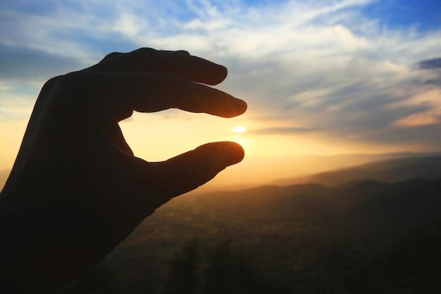 太陽と山の夕日を持っている美しいシルエット手。力と希望のコンセプト。