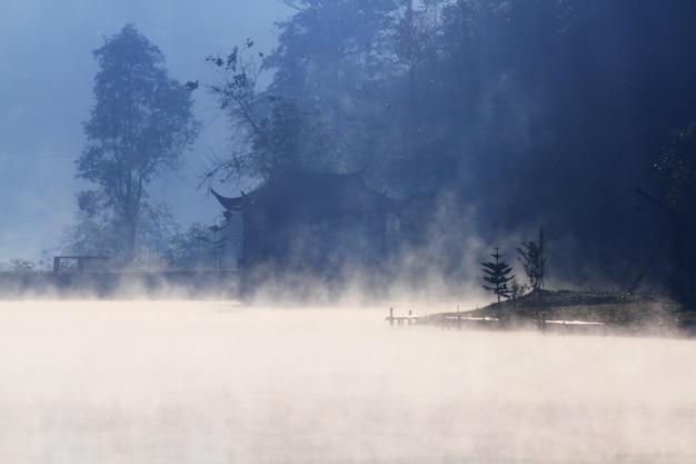 霧と霧の湖の美しい風景天国とタイの山の山岳民族の村で水面に青い空の反射で輝く日の出