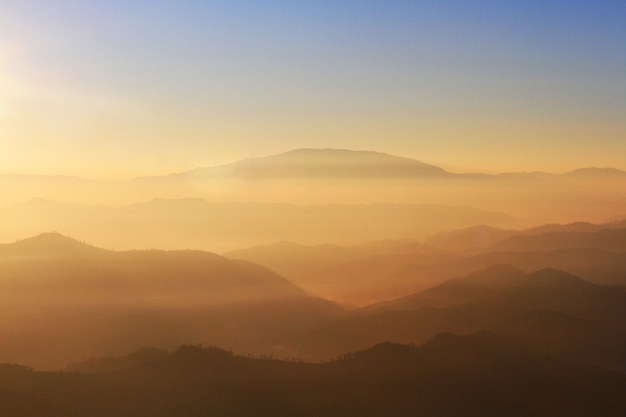 Красивый закат и восход солнца на небе и золотые сумерки время с туманом и туманом в долине горного слоя