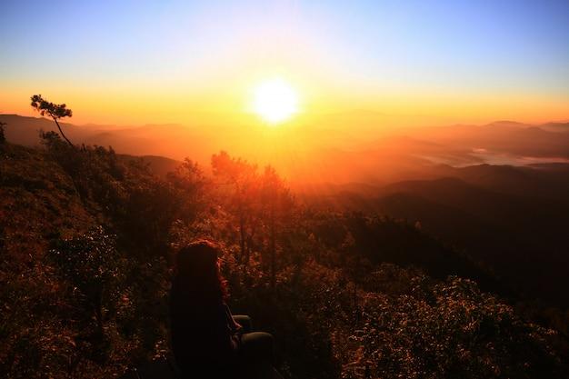 自然な黄金日の出で一人で座っているアジアの女性のシルエット