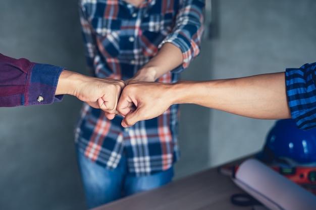 役員のチームワークは幸せで、仕事の仕上げの成功を祝うために握手する