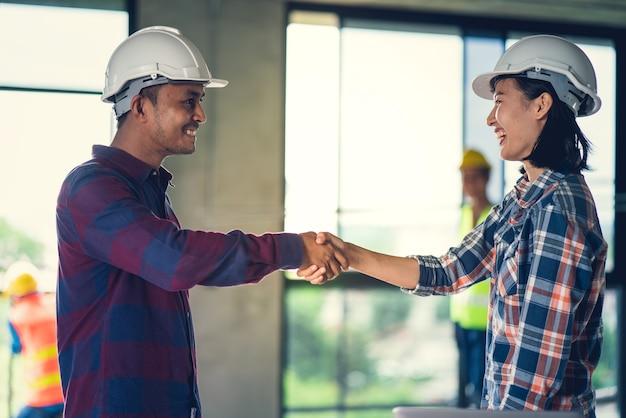 役員のチームワークは成功の家の建物の建設で祝うために幸せと握手です