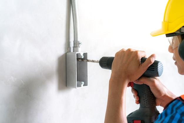 電気工事用ドリルドライバーを使用して住宅改修工事の電気接続箱に固定する