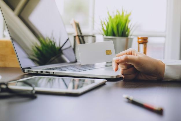ビジネスウーマンを使用してコンピュータでオンラインショッピングをするラップトップとタブレット