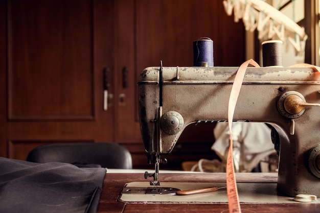 Античная швейная машина на старом деревянном столе в старом портном магазине