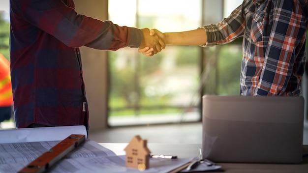 役員のチームワークは成功建設プロジェクトで祝うために幸せと握手です