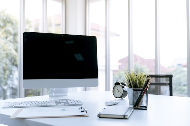 コンピュータのラップトップとホームオフィスに置かれた現代の白い机の作業台