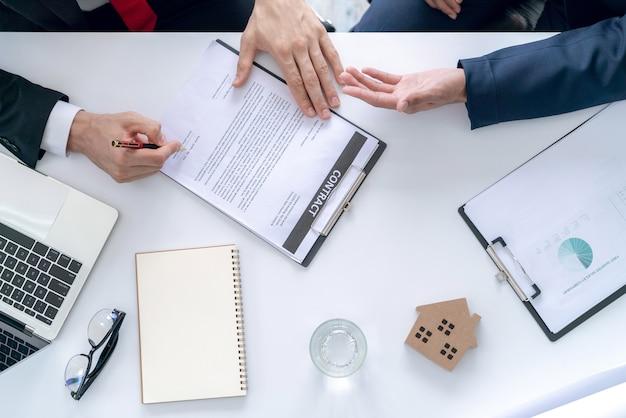 Бизнесмен и покупатель домашнего покупателя договорились о сделке и заключили договор о продаже недвижимости