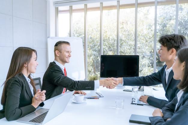 ビジネスマンの握手は契約会社に合弁してベンチャーに参加することに同意します