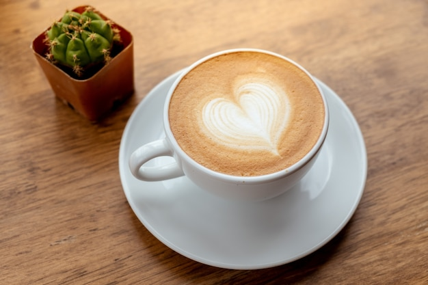 木製のテーブルの白いカップのコーヒーラテアートのハート型