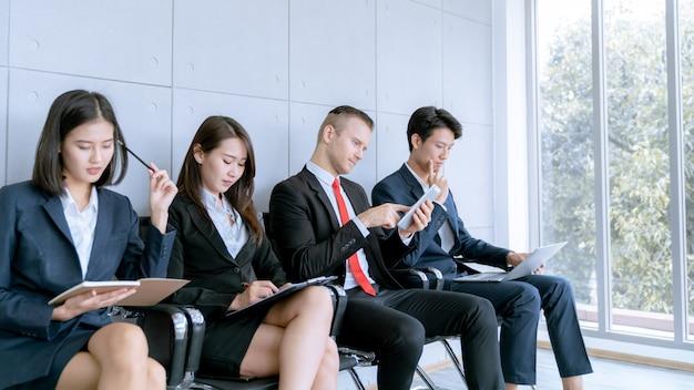 Заявитель сидит, чтобы подготовиться к собеседованию на работу в публичной компании в офисе