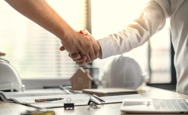 役員チームワークは幸せであり、仕事計画の仕上げの成功を祝うために握手します