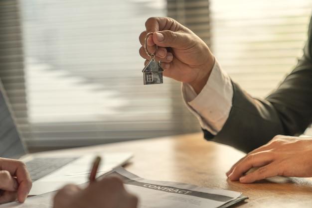 青年実業家と住宅購入者の顧客は一緒に目標を達成し、契約に署名しました。