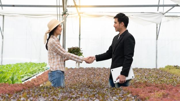 ビジネスマンおよび農夫は農場で取り引き品質の製品水耕野菜のために手を振る
