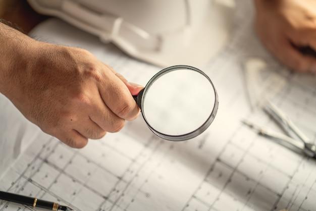 虫眼鏡に手を当てて、コンセプトが建設建物のコストを見積もるように