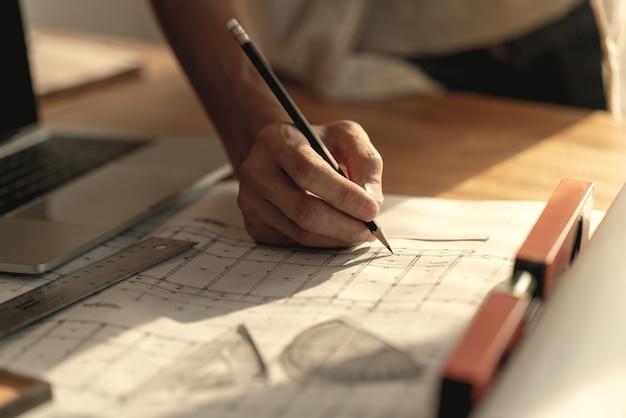 現代の家の建築設計における建築家の創造的な思考の鉛筆に手
