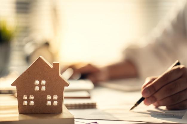 不動産や住宅購入に投資する利子、税金、利益を計算するビジネスマン