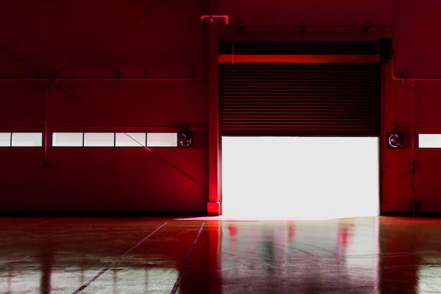 太陽からの光が付いている金属の工場ドア。カラーツールを赤色カラーフィルターに変更してください。