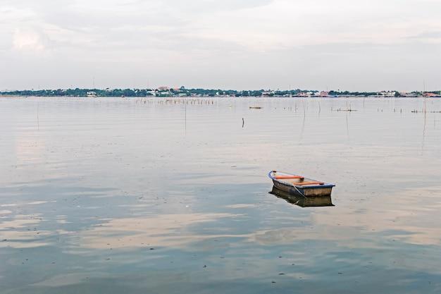 Мусор и мусор, плавающие на поверхности с разбросанным старым кораблем. с фоном города.