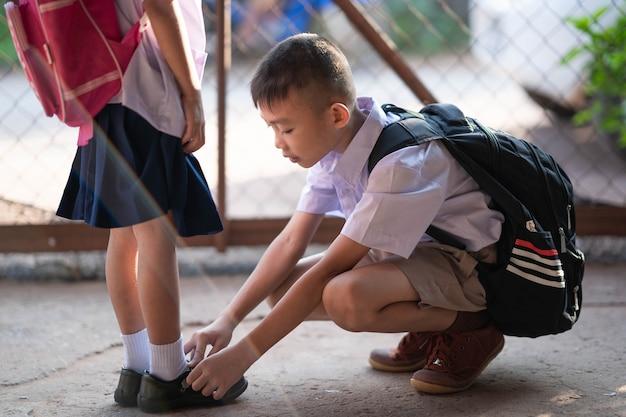 朝、学校に行く前に靴を履いている姉妹を助ける兄弟