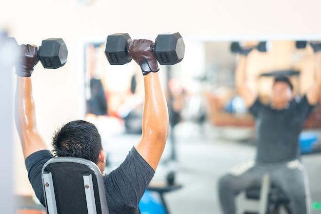 男性はジム運動フィットネスクラブセンターでダンベルを運動する