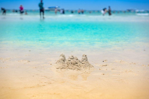 夏のビーチと緑の海で遊ぶことのための砂の山