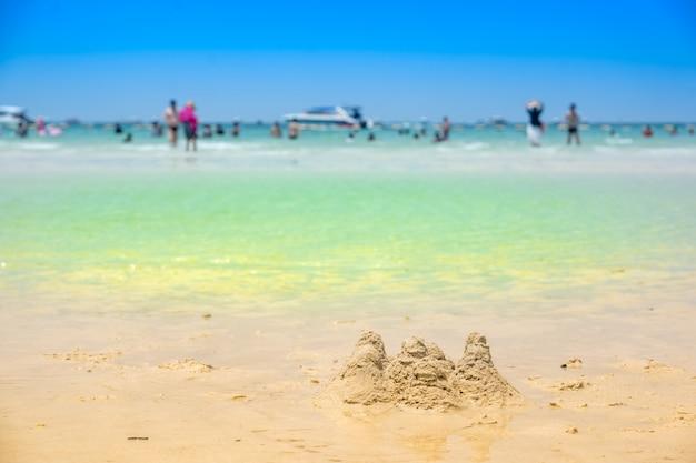 青い空に夏の緑の海のビーチでのプレーのための砂の山