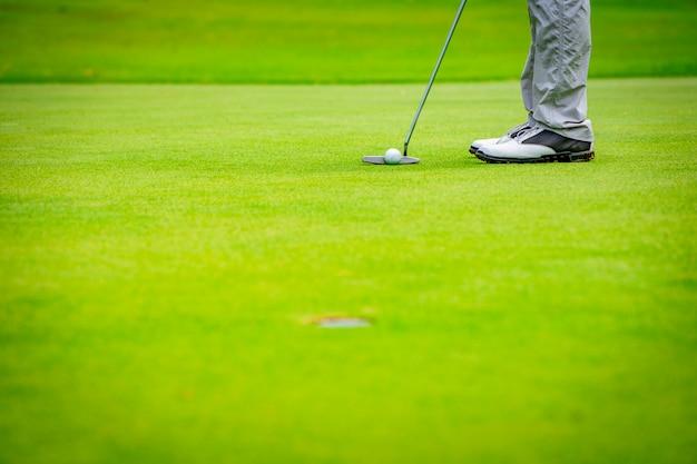ゴルファーがホールショットにゴルフボールを入れて