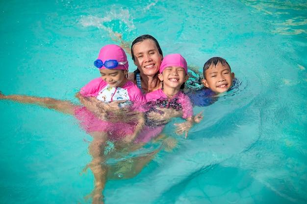 Семья плавает и играет в бассейне летом