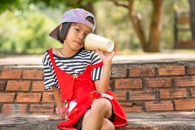 草原の牧草地の自然の屋外に紙コップから水を飲んで遊んで幸せな子供